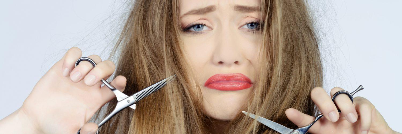 mulher triste com cabelos quebradiços e tesouras nas mãos